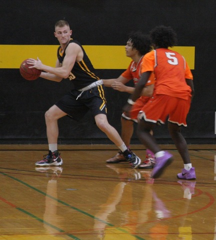 SUNY Broome men's basketball player looking to make a pass over two defenders