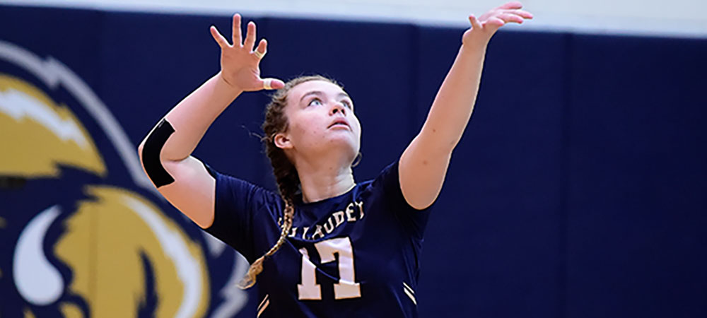 Gallaudet women's volleyball player Emma Giuntoli reaches up to serve the ball. She is wearing a dark blue Gallaudet uniform with GALLAUDET in gold letters across the front and the number seventeen in white letters below.