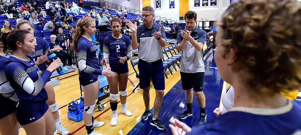 Gallaudet women's volleyball team huddles up during a timeout. Coach Boren and Assistant Coach Cory Behm communicate to the team.