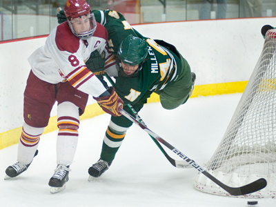 Cody Chupp fends off Northern Michigan's TJ Miller for the puck during Friday's overtime tie. (Photo by Ed Hyde)