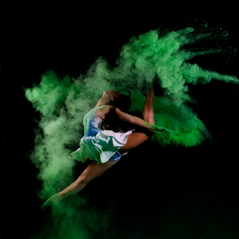 A dancer jumps while green chalk flies in the air.