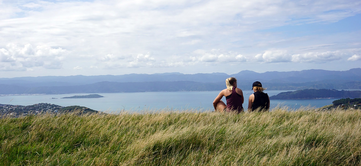 Bridget Cott and a friend sitting on a cliff in New Zealand.