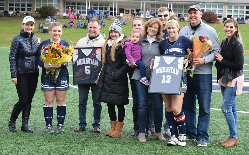 Seniors Emily Duddy and Elizabeth Hrehovcik with the families on Senior Day prior to the Greyhounds' match versus Goucher College on John Makuvek Field.