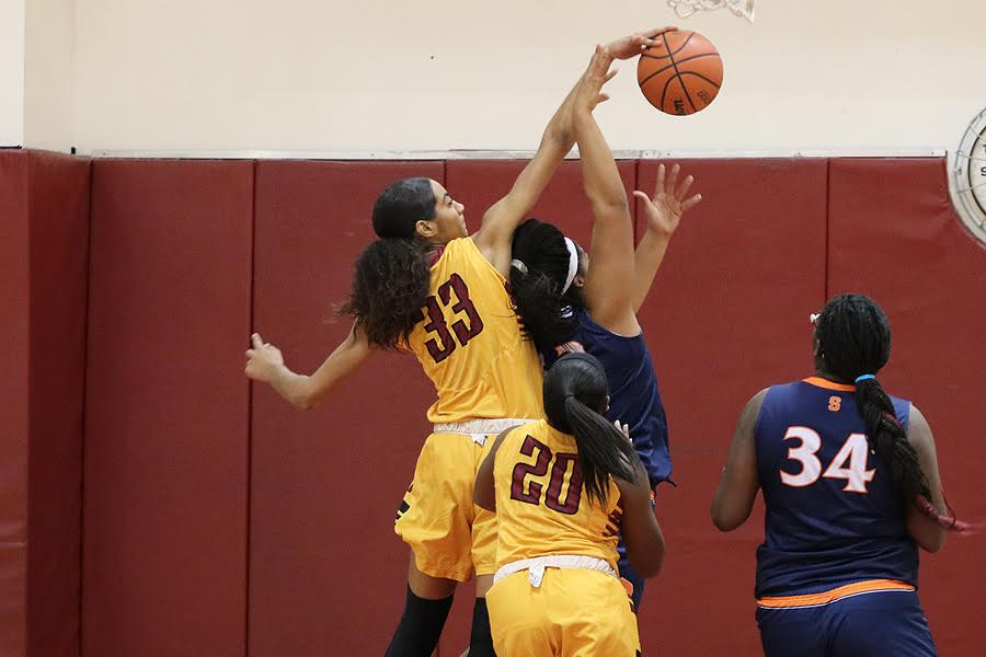 Kailyn Gideon, sophomore center, blocks a shot in a recent game, image by Richard Quinton.