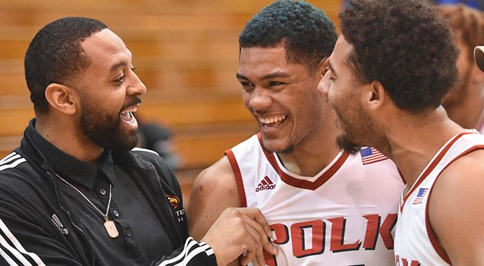Assistant Coach Ramone Shepard (left) and guard Richard Gaetano (right) congratulate Troy  Simons after his three-pointer gave the Eagles an 83-82 win over St. Petersburg. (Photo by Tom Hagerty, Polk State.)
