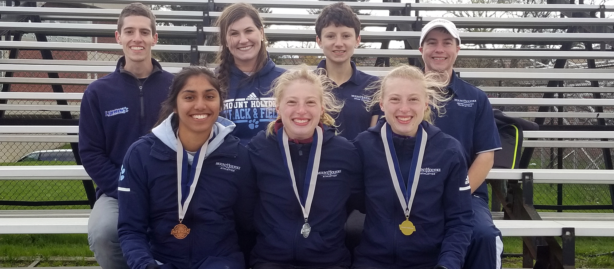 NEWMAC Medalists (Front Row) right to left: 10000m champion Hannah Rieders, 10000m runner-up Madeline Rieders, 1500m third place Simone Jacob. Back row featuring Mount Holyoke coaches.