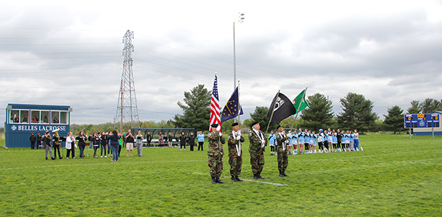 Four veterans present the colors prior to the start of a lacrosse game with the team, wearing light blue, visible in the background. A band of a dozen people play the National Anthem on the left side of the image.