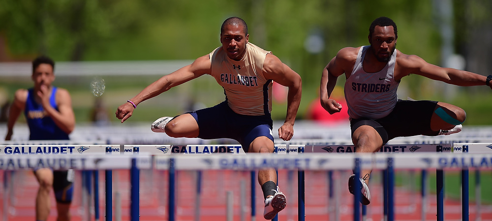 Gallaudet University men's track and field hurdler Michael Haynes clears a hurdle in a race during a sunny afternoon on the track. Go Michael!