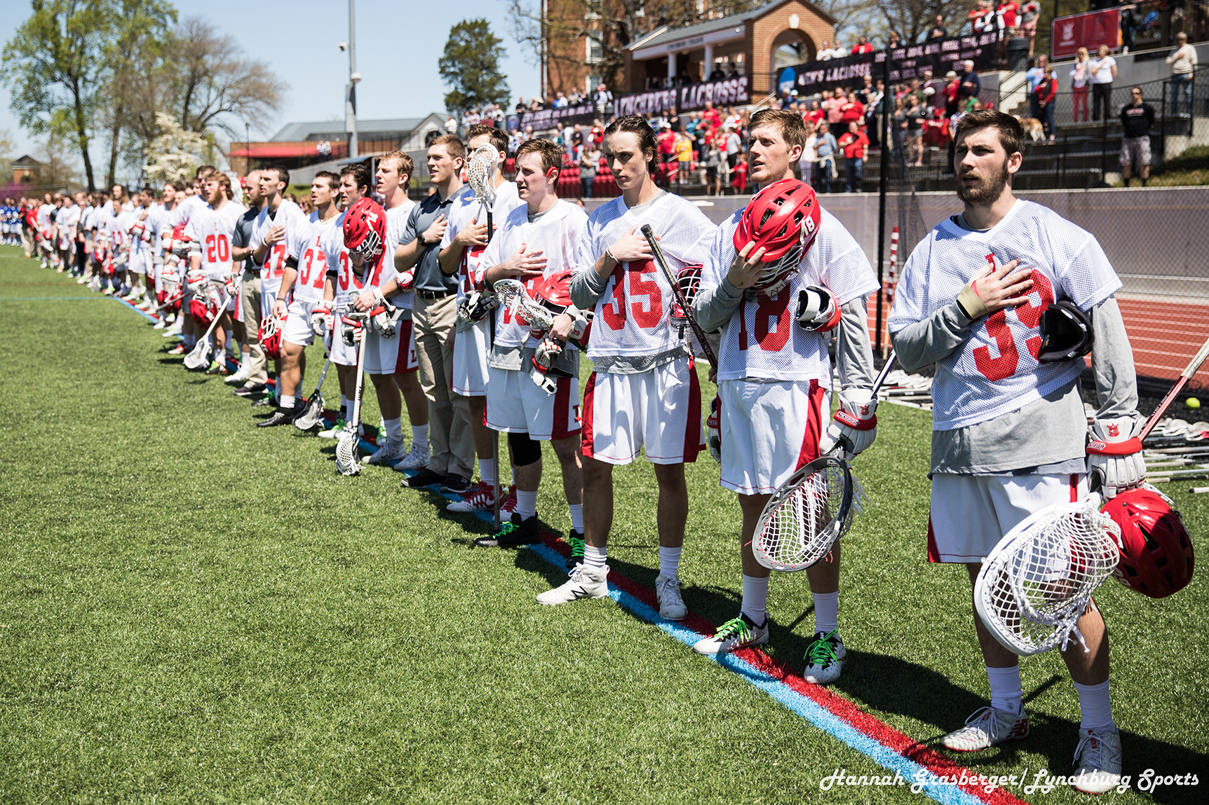The men's lacrosse team salutes the flag during the Star Spangled Banner.