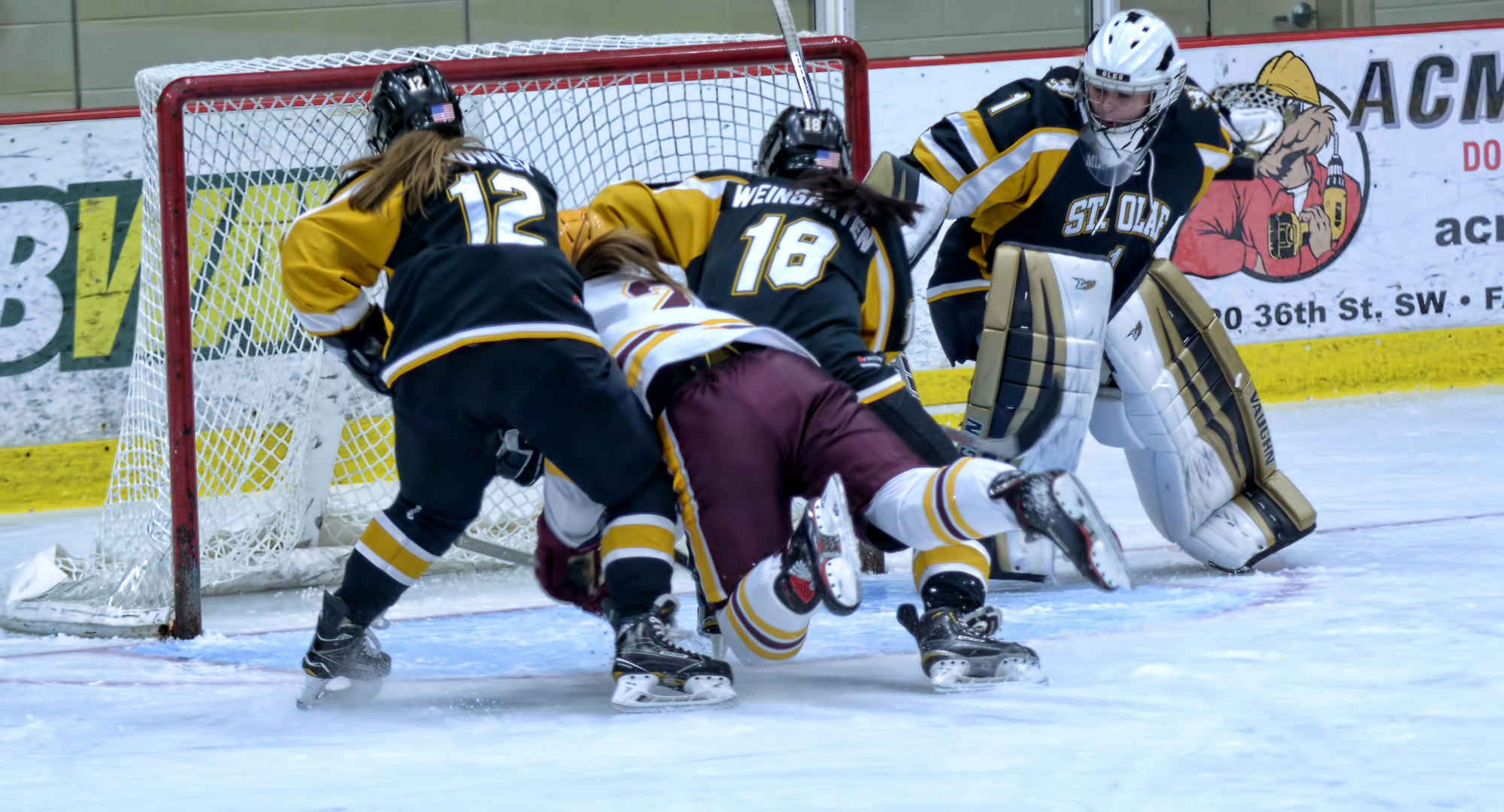 Amanda Flemming dives between two St. Olaf players to tap in a goal during the second period of the Cobbers' 5-3 win over the Oles.