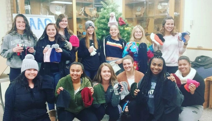 Softball team makes donations to the glove and hat drive
