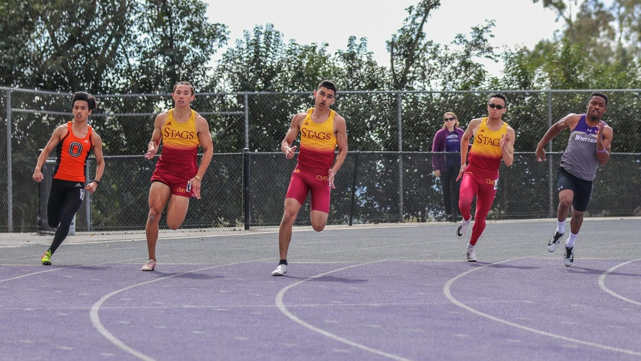 Action shot of three CMS runners taking the turn on the track