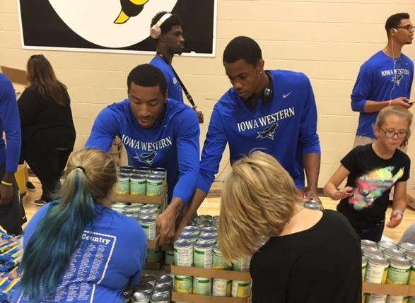 Left to Right: Freshmen Willard Anderson, Seneca Louis, Marques Watson, and Andre Silva were among the Men's Basketball Team that helped with the Council Bluffs Food Pantry Giveaway Monday evening (9/17/18).