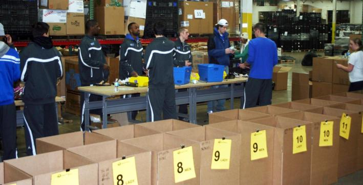 Men's Basketball helps Soles for Jesus package shoes for Africa