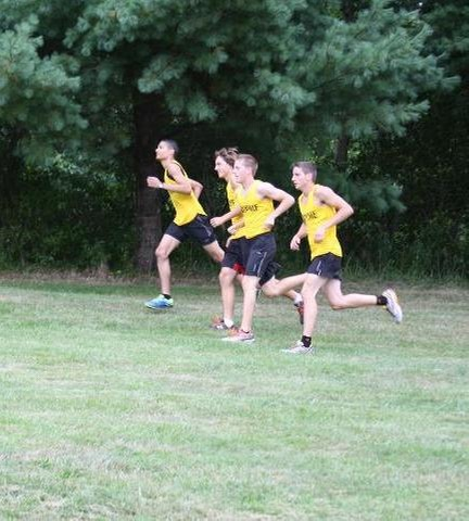 Men's cross country team running on side of hill