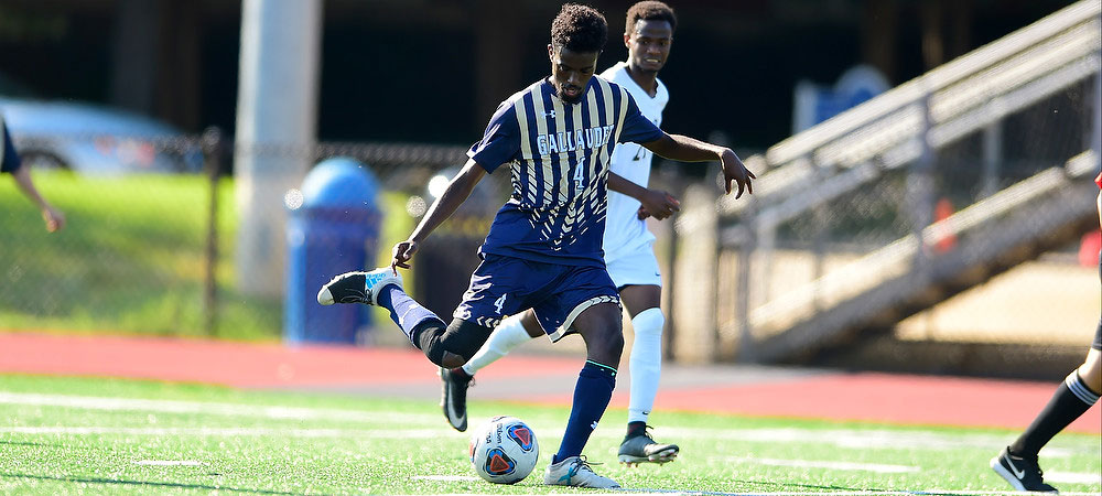 Gallaudet men's soccer play Ahmed Mahmoud dribbles the ball during a game. He is wearing a dark blue striped gold Bison uniform with the number four and GALLAUDET in white letters on the front.