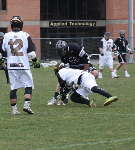 Broome lax player diving on ground for ball