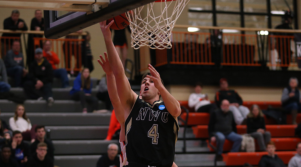 Nate Bahe finishes a layup for Nebraska Wesleyan with a Wartburg defender trailing. (Photo by Ryan Coleman, d3photography.com)