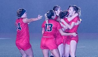 Kat Sheehy, right, is mobbed after scoring the game's only goal on a header in the 59th minute. (Photo by Ken Sciallo / Sevilla Photography)