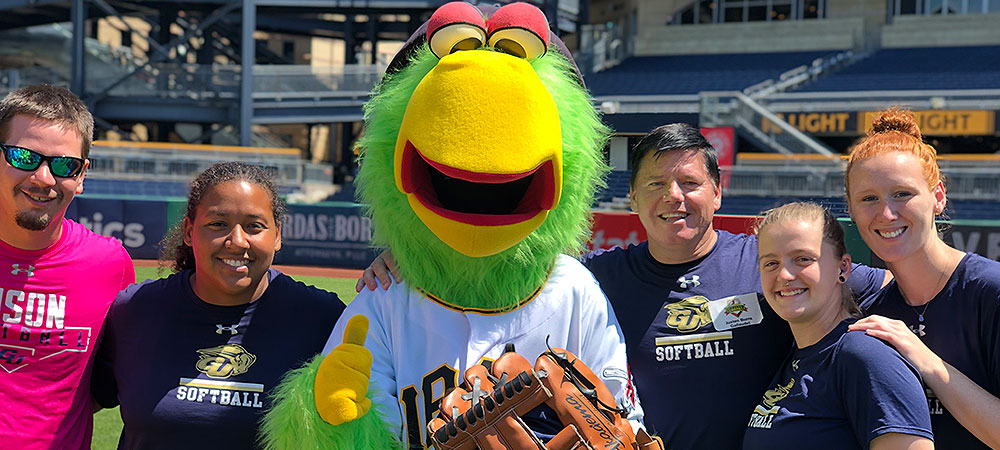 Group of Gallaudet softball coaches and students pose for a group photo with the Pittsburgh Pirates mascot the Parrot on a sunny afternoon.