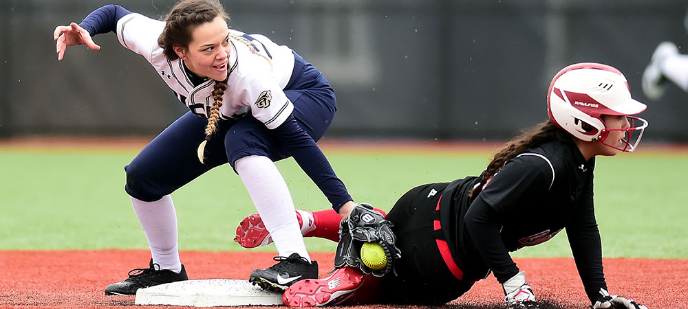 Irene De Luna applies a tag on a Catholic runner, who slide into second base.