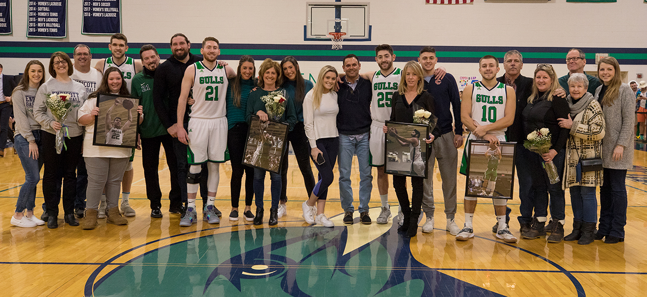 Families pose for a senior day photo.
