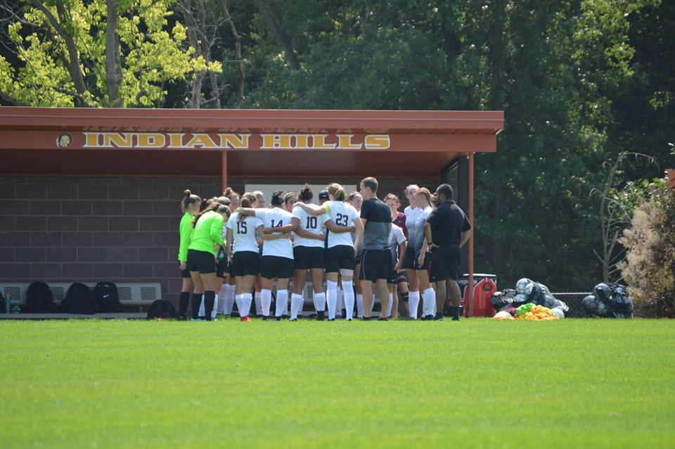 Women's Soccer Team huddled together strategising before the game.