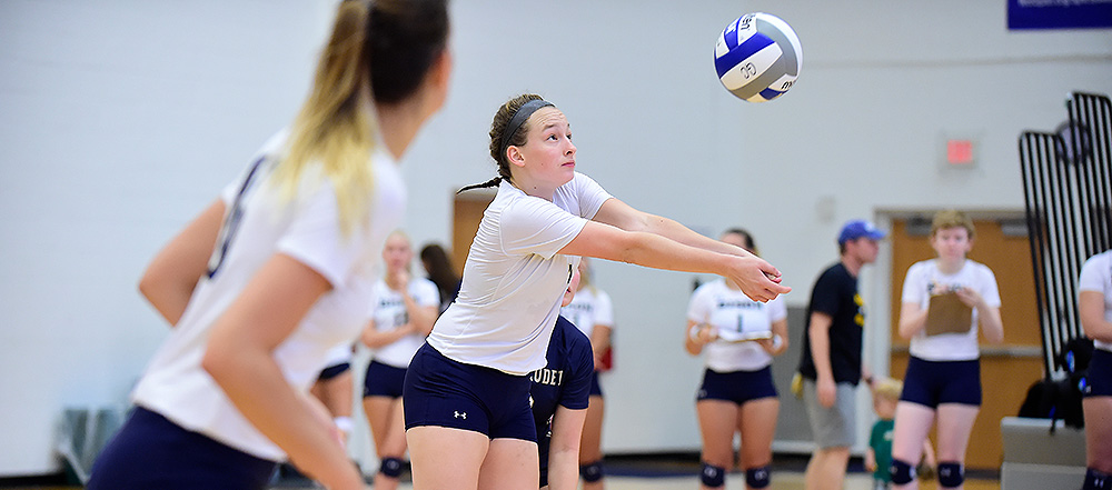 Women's volleyball player Farah Harmount digs the ball.