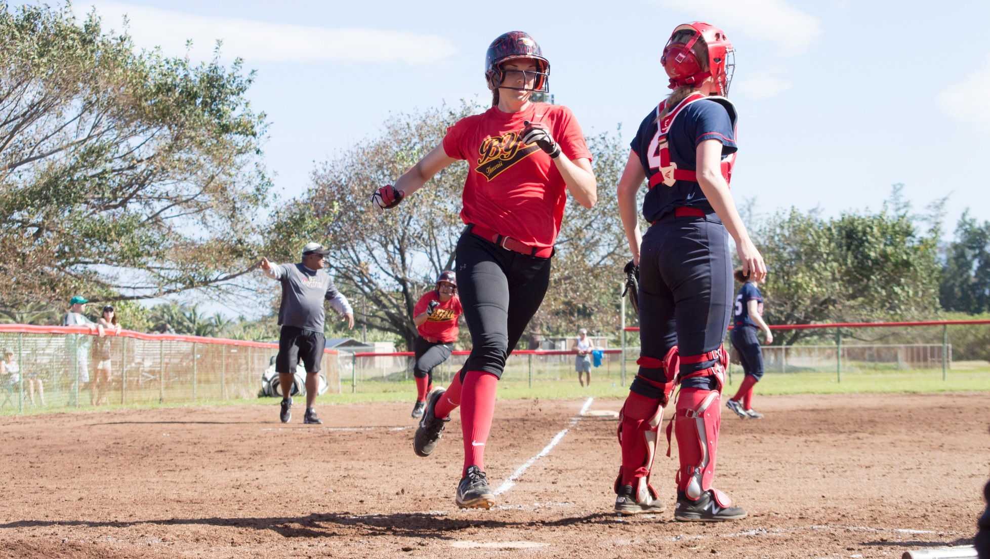 Meghan Wantz and Sarah Captain cross the plate off Lizabelle Talataina's single in the bottom of the seventh inning.