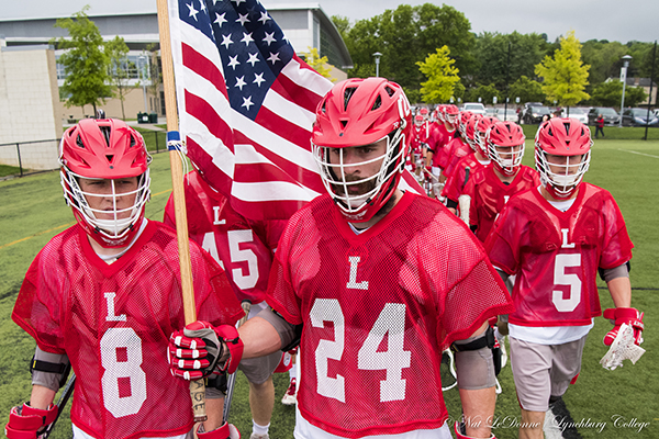 Men's lacrosse players carry the American flag onto the field before a game.