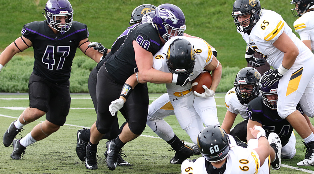 Dalton Heckel of UW-Whitewater wraps up UW-Oshkosh ballcarrier JP Peerenboom. (Photo by Daryl Tessmann, d3photography.com)