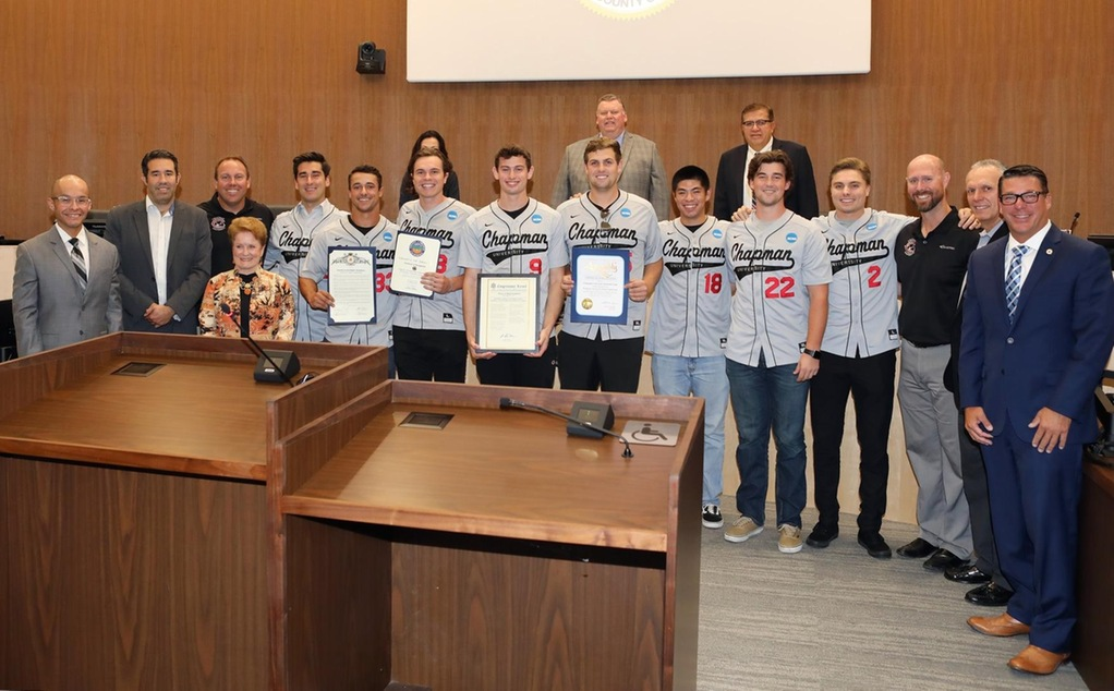 Members of the baseball team and representatives of local elected officals pose for a picture with the Orange City Council.