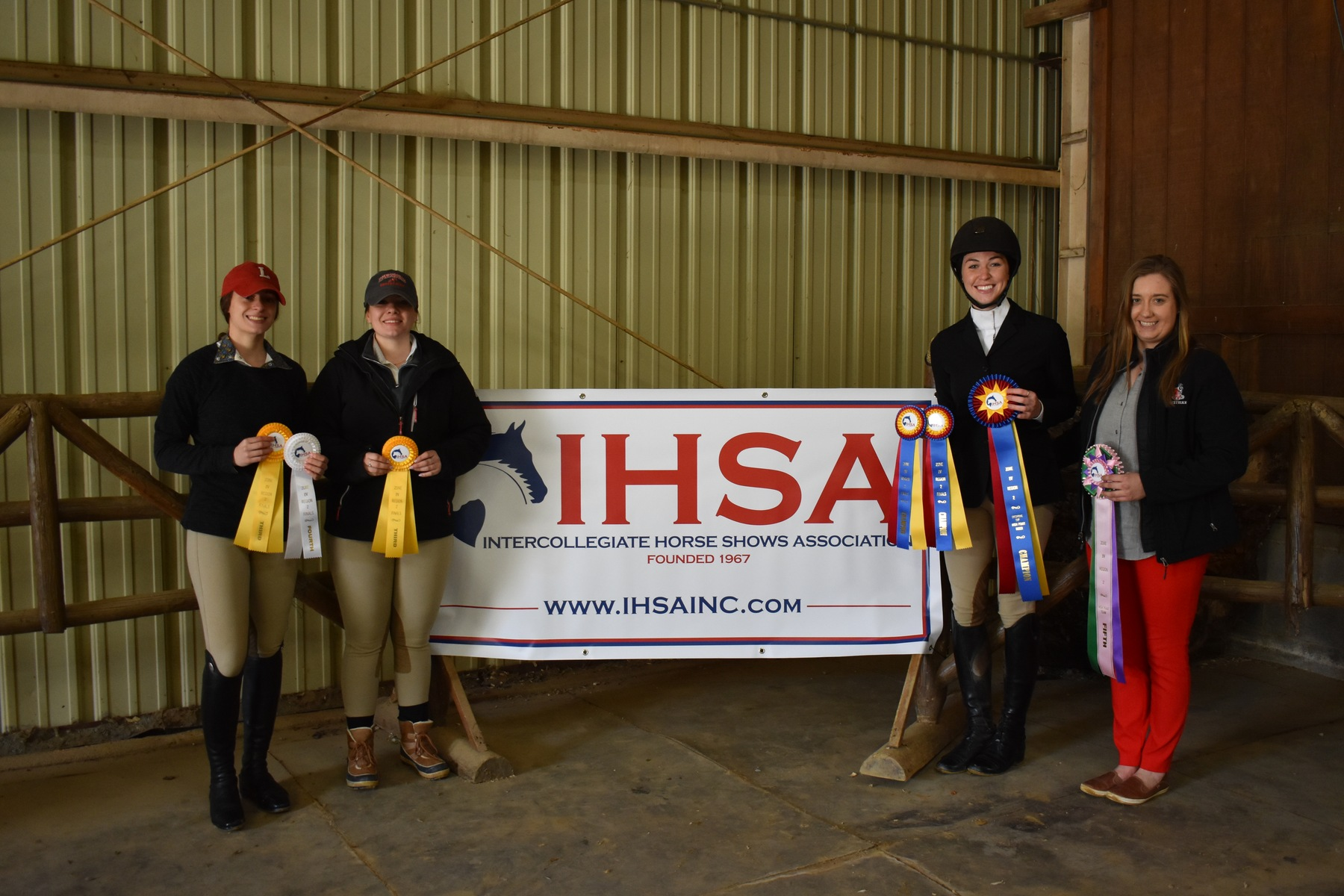 Riders pose by the IHSA sign with their award ribbons.