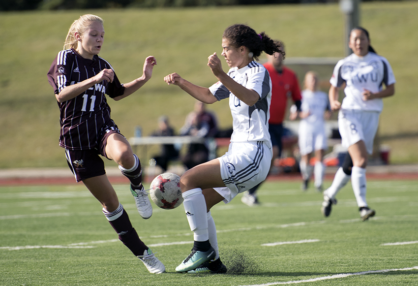 Raeghan McCarthy battles for the ball with a Trinity Western defender on Sunday (Chris Piggott photo).