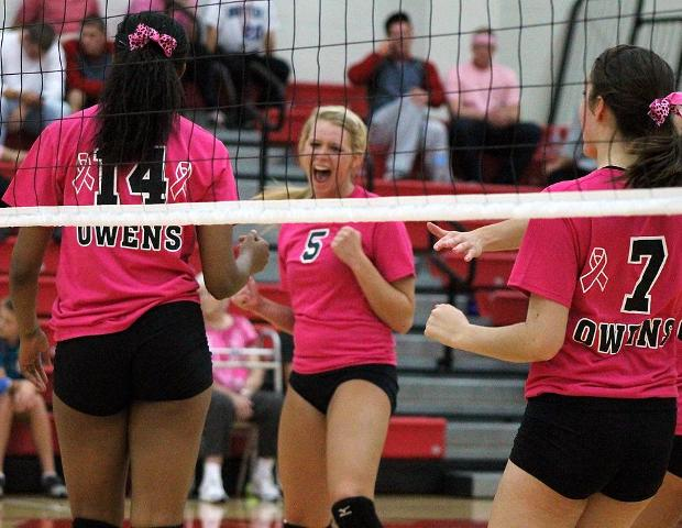 Jessica Cooper (5) celebrates a point with Jazmine Thomas (14) and Bailey Dangler (7) in tonight's straight set win over Cuyahoga Community College. Photo by Nicholas Huenefeld/Owens Sports Information
