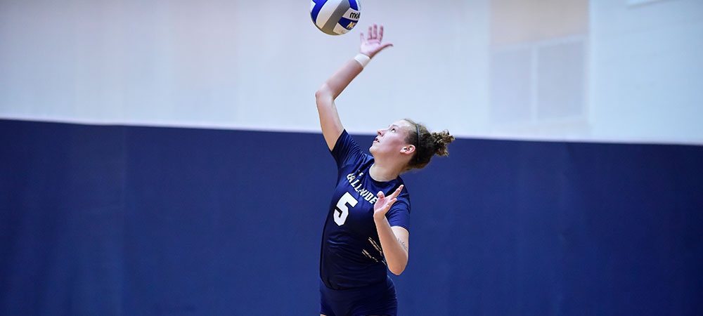 Gallaudet women's volleyball player Adele Daniels reaches for the ball in an attack attempt. She is wearing the dark blue Gallaudet volleyball uniform with GALLAUDET in white letters across the front, above the number five.