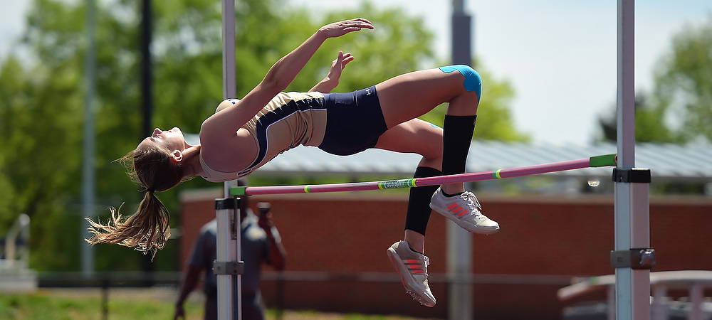 Gallaudet women's track and field jumper Hannah Wetzel makes a jump in the high jump event on a sunny afternoon at Thomas O. Berg Track. She clears the bar as she flies backwards over the bar onto a huge cushion.
