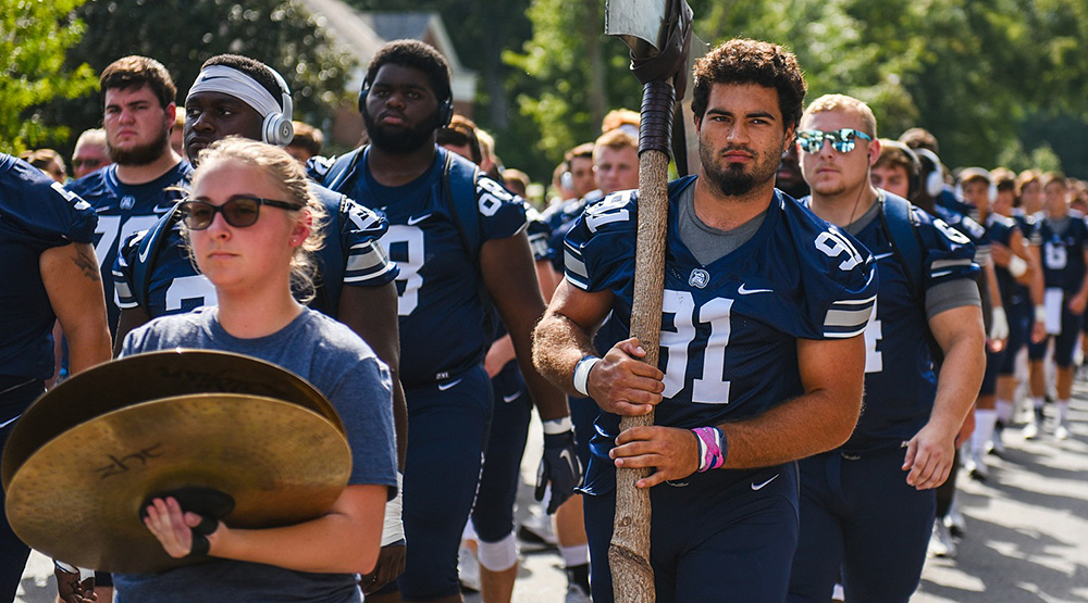 Berry's Bryson Lamboy, carrying a large ax, follows a crash cymbals player and leads a line of Berry Vikings in uniform before the team's season opener. (Berry athletics photo)