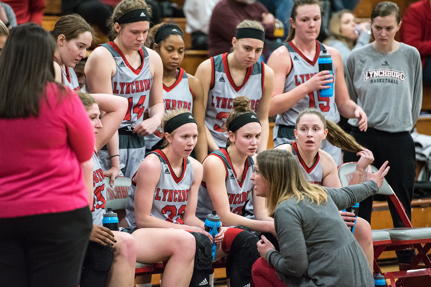 Lynchburg women's basketball watches Coach during a timeout.
