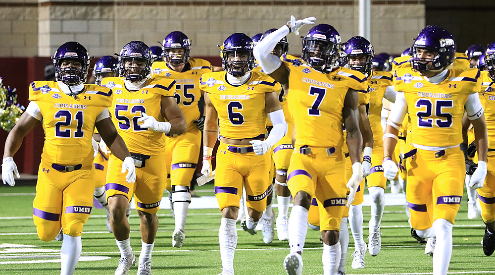 Mary Hardin-Baylor, including seniors Markeith Miller, Santos Villarreal, Reggie Cole and Raylon Hickey, take the field before Stagg Bowl XLVI. (Photo by Joe Fusco, d3photography.com)