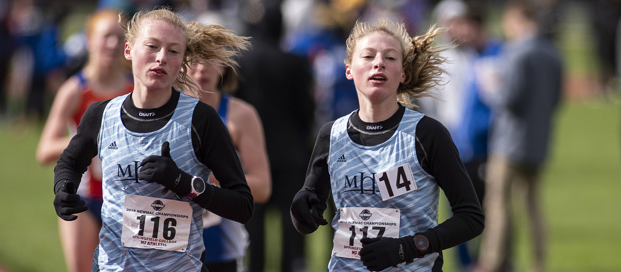 Action photo of Hannah and Madeline Rieders in the 10,000-meter run at the 2019 NEWMAC Championships. Photo courtesy of Frank Poulin.