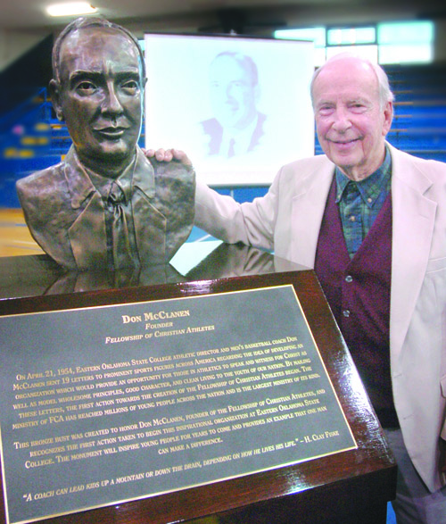 Don McClanen stands with a bronze sculpture at an unveiling ceremony at Eastern.
