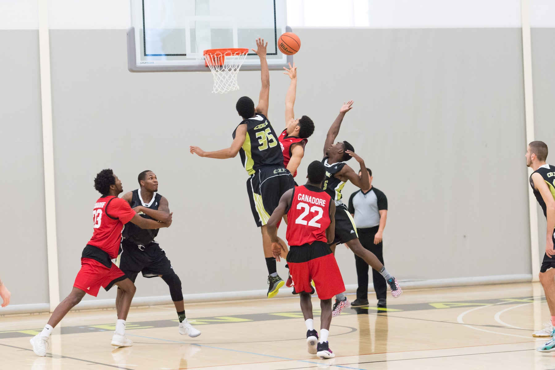 Colts men's basketball player Malcolm Jackson attempts to block the opposing Canadore player.