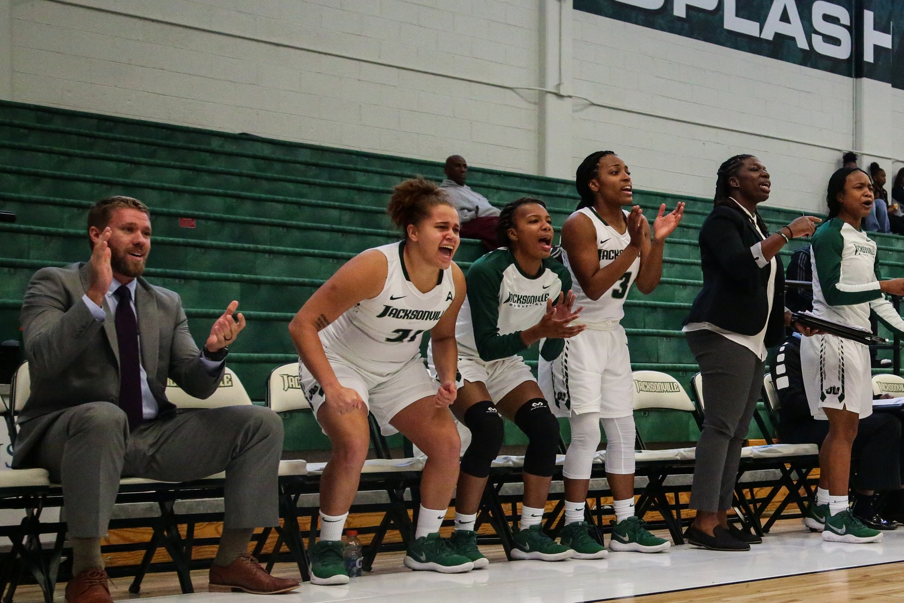 PLayers on women's basketball bench cheering