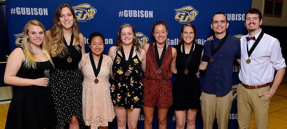 Gallaudet Athletics' Chi Alpha Sigma Induction Class of 2019. Group photo of eight people in front of the #GUBison backdrop.
