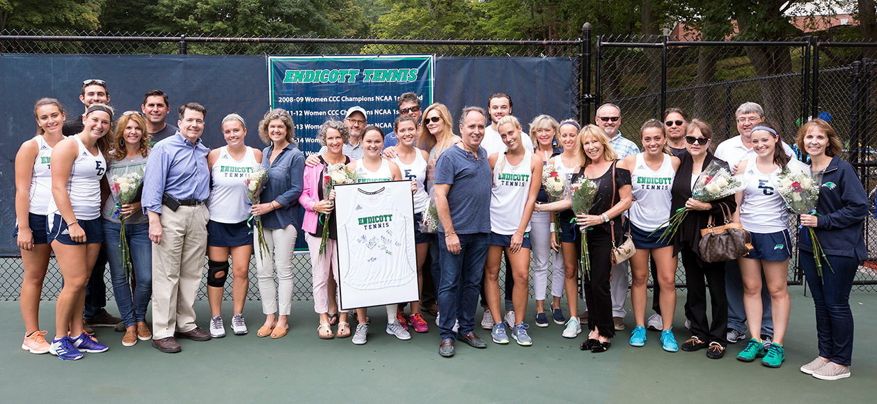 Women's tennis seniors and their families pose for a photo.