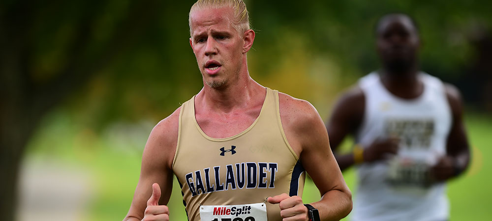 Gallaudet men's cross country runner Gunner Hahn runs at the Towson meet. He is wearing the Gallaudet gold uniform with his number pinned to the front, and GALLAUDET in dark blue letters on the front of the tank top.