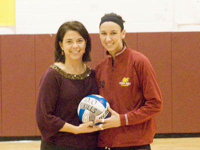 Ferris State women's volleyball head coach Tia Brandel-Wilhelm presents Kristy Gilchrist with a ceremonial ball honoring her 1,000th career kill. (Photo by Joe Gorby)
