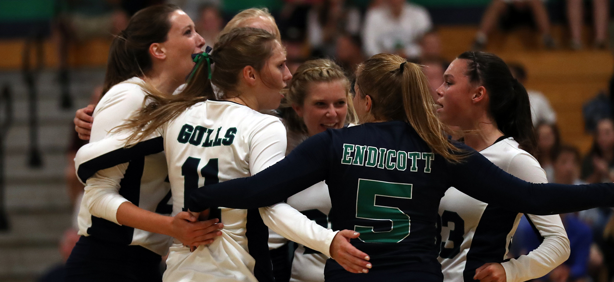 Image of the women's volleyball team bringing it together on the court after winning a point.