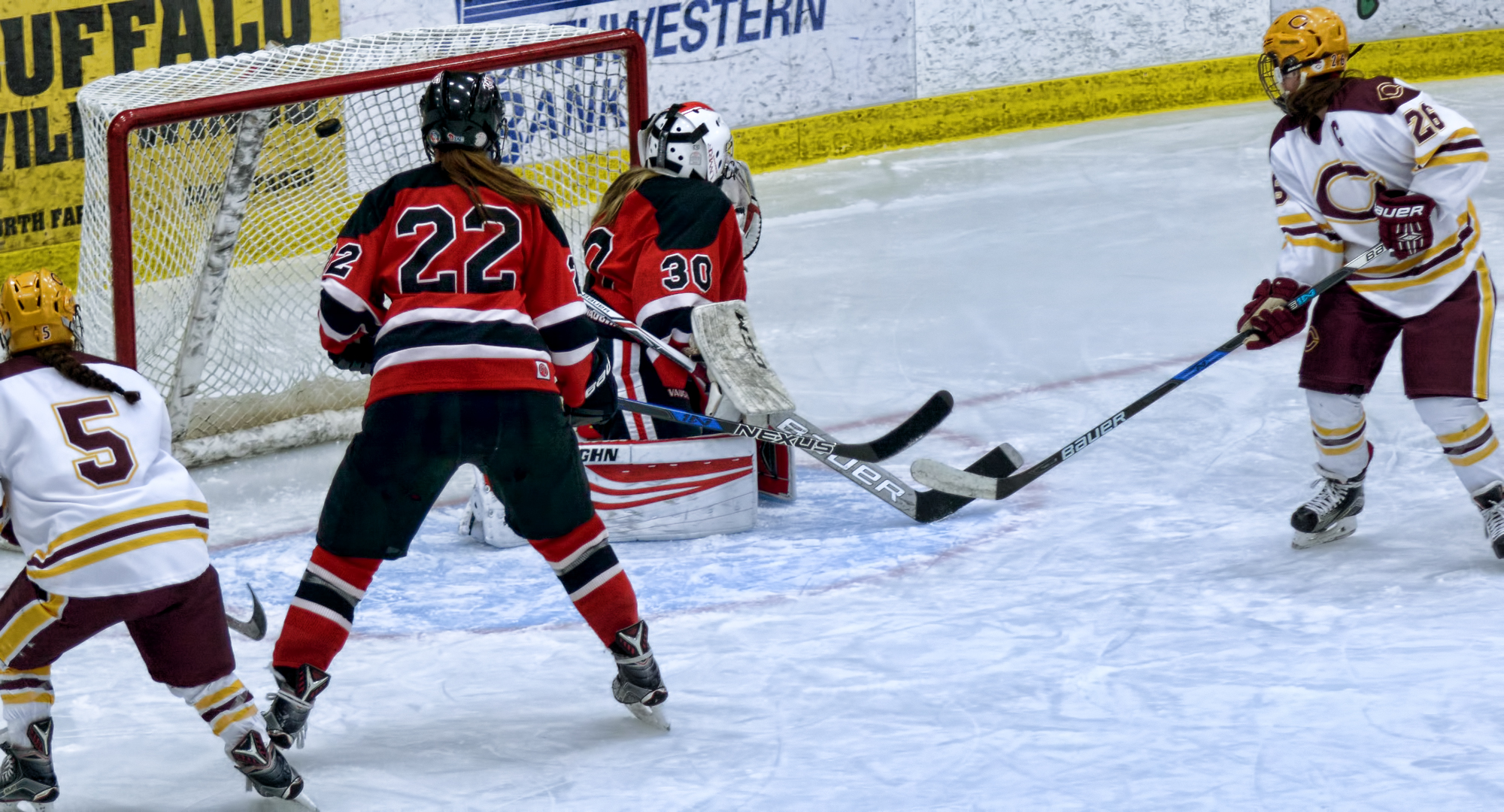 Tori Davis (#26) and Josee Lundgren (5) watch the puck fly into the net after teammate Callie Fagerstrom's shot in the third period against #6 Wis.-River Falls.